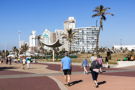 beach front: DURBAN, SOUTH AFRICA - JUNE 26, 2016: Many early morning unknown people on paved promenade on Golden Mile beach front against city skyline in Durban, South Africa