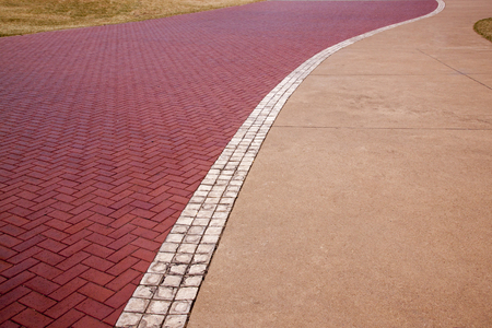 walkway: Above view of concrete and red paved  patternes and textures on promenade with grass edges and white center line Stock Photo