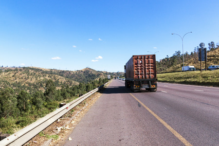 gauteng: Heavy duty container truck travelling along highway between Durban and Gauteng in South Africa