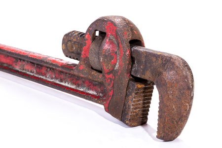 neglected: Studio shot close up left  front view of vertical old neglected rusty well used red monkey wrench spanner on white background
