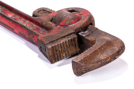 Studio shot close up left  front view of  old neglected rusty well used red monkey wrench spanner jaws on white background
