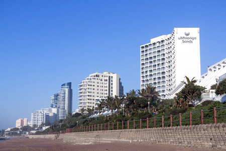 UMHLANGA, DURBAN, SOUTH AFRICA - JULY 8, 2016: Empty beach and concrete retaining wall  on early morning beach front against commercial and residential complexes in Umhlanga Rocks Banco de Imagens - 59346401