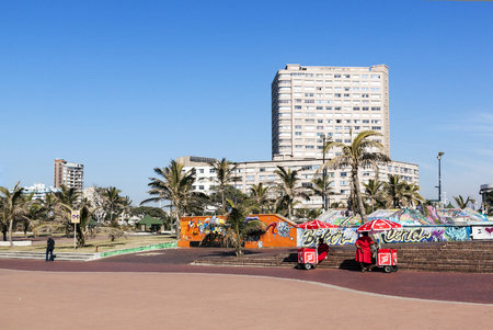 beach front: DURBAN, SOUTH AFRICA - JUNE 26, 2016: Early morning  unknown person and ice cream vendors on promenade against city skyline on beach front in Durban, South Africa