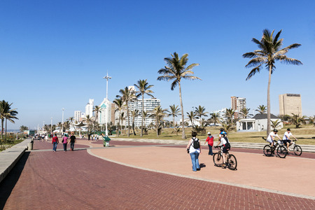 DURBAN, SOUTH AFRICA - JUNE 26, 2016: Many early morning unknown people and cyclists on paved promenade on Golden Mile beach front against city skyline in Durban, South Africa