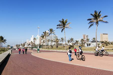 empedrado: Durban, Sudáfrica - 26 de junio, 2016: Muchas personas y ciclistas en paseo pavimentado frente a la playa Milla de Oro contra horizonte de la ciudad en Durban, Sudáfrica desconocidos de la madrugada