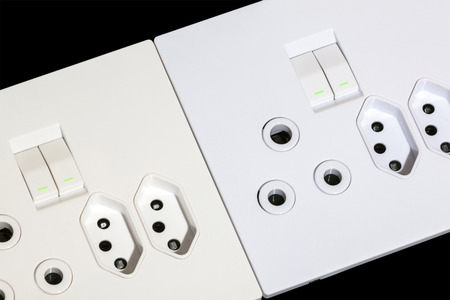 sockets: Close up of beige and white multipurpose wall mount sockets and switches on black Stock Photo