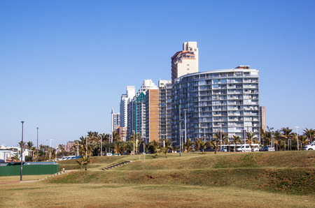 comercial: DURBAN, SOUTH AFRICA - AUGUST 25, 2016: Empty lawn area against comercial and residential buildings on Golden Mile beach front city skyline in Durban, South Africa