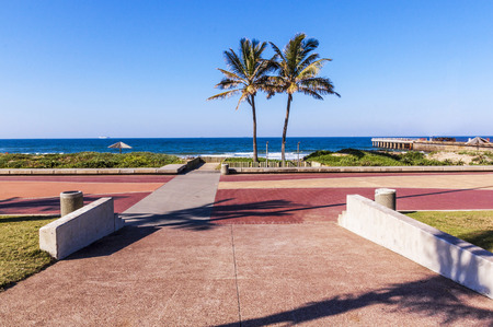 Empty on ramp over paved promenade leading toward  palm trees ocean and skyline in Durban, South Africa Stock Photo