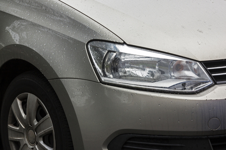 front end: Close up of  left view front end of wet motor vehicle covered with rain droplets on wheel tyres bonnet and front grills patterns and textures Stock Photo