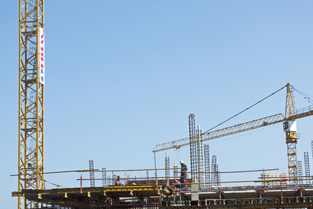 metal structure: MHLANGA RIDGE, DURBAN, SOUTH AFRICA - OCTOBER 21, 2016: High lift crane and many unknown people working amongst scaffolding and concrete structures with reinforcing bars extending above work area