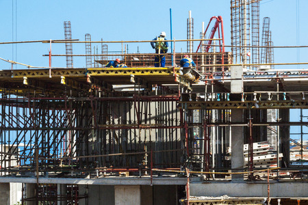 MHLANGA RIDGE, DURBAN, SOUTH AFRICA - OCTOBER 21, 2016: Close up of many unknown workers working amongst scaffolding and concrete on construction site Editorial