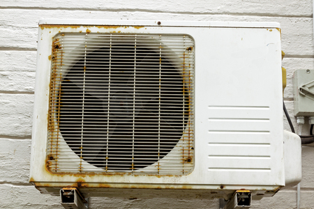 needing: Old vintage rusting metal exterior fitted airconditioning unit mounted on wall needing maintenance