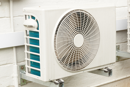 Single weathered white airconditioning unit mounted on exterior home wall