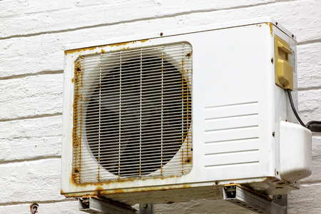 fitted unit: Old vintage rusting metal exterior fitted airconditioning unit mounted on wall needing maintenance