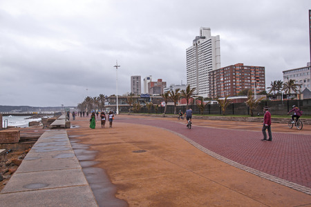 beachfront: DURBAN, SOUTH AFRICA - OCTOBER 30, 2016: Many unknown people walking along  paved promenade at North Beach on Golden Mile beachfront on overcast wet afternoon in Durban Editorial