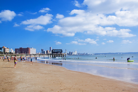 DURBAN, SOUTH AFRICA - APRIL 28, 2016: Many unknown people  enjoy morning visit to Vetchies  beach on Golden Mile beachfront against city skyline in Durban, South Africa