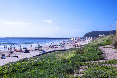 DURBAN, SOUTH AFRICA - APRIL 28, 2016: Many unknown people  enjoy morning visit to Vetchies  beach on Golden Mile beachfront against harbor entrance and Bluff  in Durban, South Africa