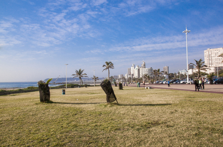 beachfront: DURBAN, SOUTH AFRICA : APRIl 4,  2016: Many unknown people enjoy  early morning stroll on quiet promenade on Golden Mile beachfront against city skyline in Durban, South Africa Editorial