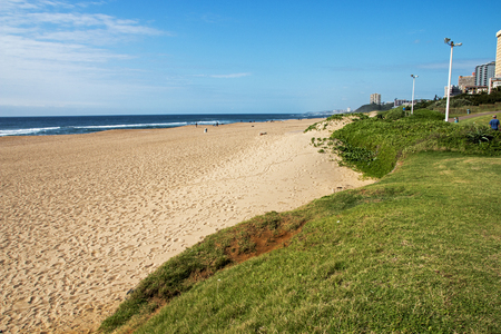Quiet early morning grass verge and empty beach against commercial and residential buildings and blue sky on beach front in Amanzimtoti in Durban, South Africa