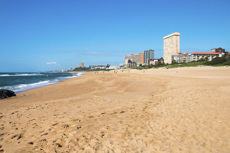 Quiet early morning empty beach against commercial and residential buildings and blue sky on beach front in Amanzimtoti in Durban, South Africa