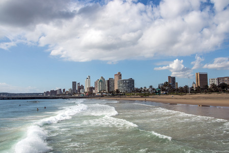 DURBAN, SOUTH AFRICA - DECEMBER 2, 2016: Many unknown people enjoy early morning visit to beach  under blue cloudy sky at Golden Mile beachfront against city skyline