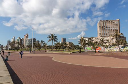 beachfront: DURBAN, SOUTH AFRICA - DECEMBER 2, 2016: Many unknown people on quiet early morning paved promenade on Golden Mile beachfront against Durban city skyline