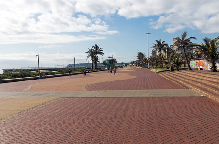 beachfront: DURBAN, SOUTH AFRICA - DECEMBER 2, 2016: Many unknown people on quiet early morning paved promenade on Golden Mile beachfront in Durban, South Africa Editorial