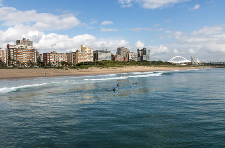 stadium  durban: DURBAN, SOUTH AFRICA - DECEMBER 2, 2016: Four unknown early morning surfers on calm sea against blue cloudy sky and golden mile city skyline in Durban Editorial