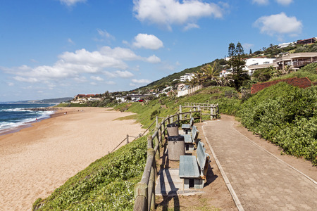 Paved walkway, green lush dune vegetation, sand,  residential housing and blue cloudy skyline at Ballito beach near Durban, South Africa Banco de Imagens
