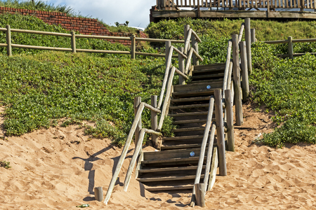 Wooden stepped entrance through green lush dune vegetation onto beach at Ballito beach near Durban, South Africa Stock Photo
