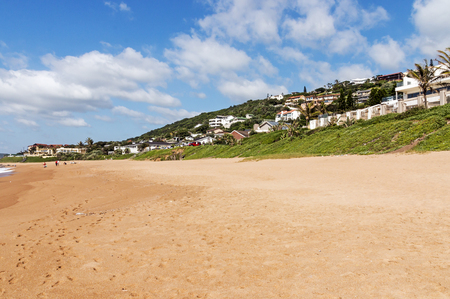Green lush dune vegetation, sand,  residential housing and blue cloudy skyline at Ballito beach near Durban, South Africa