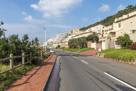 beachfront: DURBAN, SOUTH AFRICA - DECEMBER 9, 2016: Early morning empty asphalt road against beachfront buildings and  blue cloudy skyline at Umdloti in Durban, South Africa Editorial