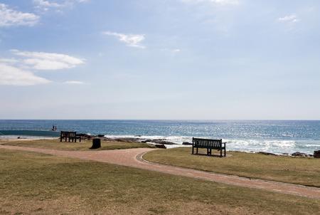empedrado: Dos bancos vacíos en borde de hierba y calzada pavimentada contra horizonte de mar y el cielo azul Paisaje Foto de archivo