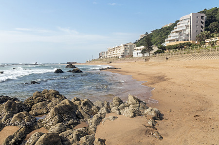 Rocks on empty sandy beach and residential buildings against blue skyline at Ballito near Durban, South Africa