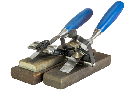 Studio shot of two chisels clamped in angle guide jigs resting on grinding whetstones on white background Stock Photo