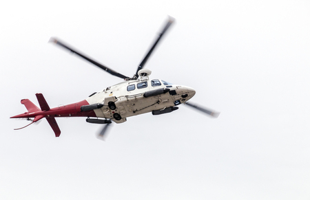 Under view of airborn helicopter isolated against white overcast sky