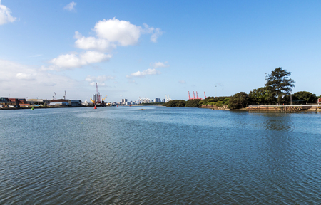 Early morning view of quiet peaceful water against harbor and blue cloudy city skyline in Durban, South Africa Stock Photo