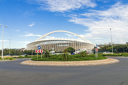 mabhida: DURBAN, SOUTH AFRICA - FEBRUARY 24, 2017: Early morning, asphalt roundabout  against Moses Mabhida Stadium and  blue cloudy sky background in Durban, South Africa Editorial