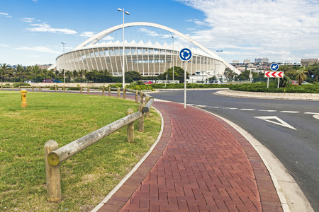 stadium  durban: DURBAN, SOUTH AFRICA - FEBRUARY 24, 2017: Early morning, Paved walkway and asphalt roundabout  against Moses Mabhida Stadium and  blue cloudy sky background in Durban, South Africa
