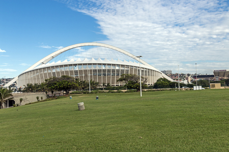 stadium  durban: DURBAN, SOUTH AFRICA - FEBRUARY 24, 2017: Early morning, green grass lawn against Moses Mabhida Stadium and  blue cloudy sky background in Durban, South Africa