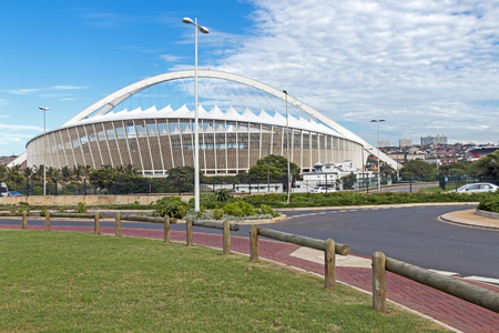 mabhida: DURBAN, SOUTH AFRICA - FEBRUARY 24, 2017: Early morning, paved promenade, green grass lawn and palm trees against Moses Mabhida Stadium and  blue cloudy sky background in Durban, South Africa