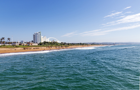beachfront: Calm sea and beach against coastal buildings and blue sky and white clouds in Durban, South Africa