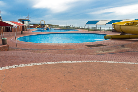 Paved promenade and beachfront recreational swimming pools against blue cloudy sky in Durban, South Africa