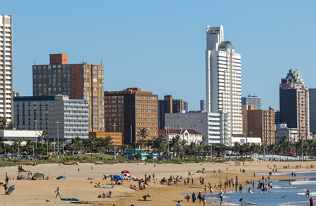 DURBAN, SOUTH AFRICA - APRIL 15 , 2017: Many unknown people on early morning beach against beachfront and city skyline in Durban, South Africa Editorial