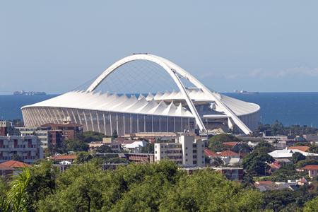 mabhida: DURBAN, SOUTH AFRICA - APRIL 16, 2017: Urban lanscape against Moses Mabhida stadium and coastal skyline in Durban, South Africa