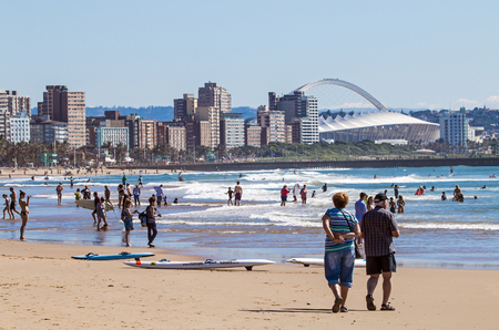 mabhida: DURBAN, SOUTH AFRICA ; APRIL 24, 2017: Many unknown people on morning visit to beach against Durban city skyline and Moses Mabhida Stadium  in South Africa