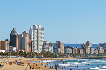 DURBAN, SOUTH AFRICA - APRIL 17, 2017: Many morning visitors, swimmers and surfers on the beach against Durban City skyline in South Africa