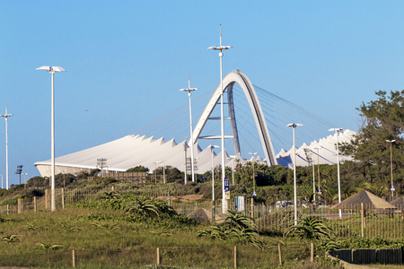 mabhida: DURBAN, SOUTH AFRICA - APRIL 21, 2017:  Early morning view of dune vegetation against Moses Mabhida Stadium and blue sky in Durban, South Africa.