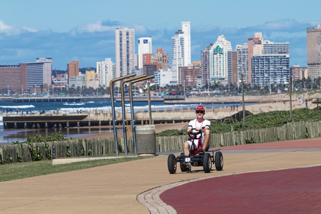 peddle: DURBAN, SOUTH AFRICA ; APRIL 15, 2017: Lone unknown man driving peddle cart on paved promenade against Durban city skyline in South Africa