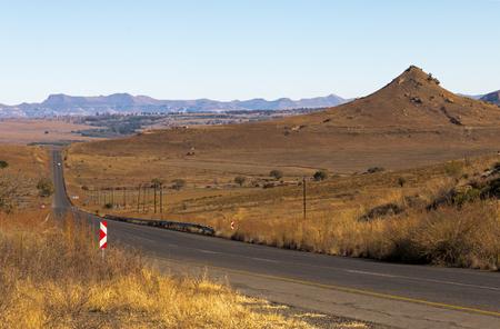 Long straight empty rural asphalt road running through dry winter landscape against blue sky horizon n Orange Free State in South Africa Stock Photo